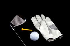 与手套球的在黑背景的高尔夫俱乐部和发球区域 免版税库存图片