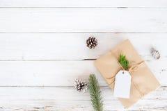 与手工制造当前礼物盒的圣诞节背景和在白色木板的土气装饰 免版税图库摄影
