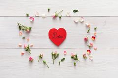 与手工制造心脏形状纸牌桃红色的华伦泰背景在玫瑰色花在白色土气木头盘旋 免版税库存图片