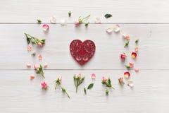 与手工制造心脏形状纸牌的华伦泰背景在桃红色玫瑰开花在白色土气木头的圈子 免版税库存照片