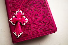 与手工制造桃红色十字架的桃红色圣经对此 库存图片