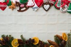 与手工制造毛毡装饰、云杉的分支、桔子和杉木锥体的圣诞节背景 在白色backgroun的圣诞节样式 免版税库存图片