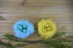 与手工制造蓝色和黄色巢的复活节装饰用在土气木桌背景的发光的箔鸡蛋填装了 免版税库存照片