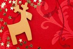 与手工制造驯鹿,金黄的星的红色圣诞节背景 免版税库存照片