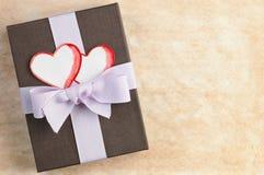 与手工纸心脏的丝带栓的礼物盒反对与空间的被弄脏的纸背景文本的 图库摄影