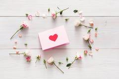 与手工纸的华伦泰背景与在桃红色玫瑰的心脏开花在白色土气木头的圈子 库存照片