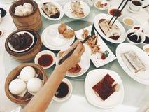与手扶的筷子的粤式点心午餐 库存图片