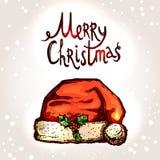 与手拉的圣诞老人帽子和印刷术的圣诞卡 库存图片