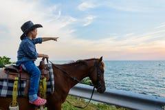 与手指出和神色的一匹男孩骑乘马向海 库存图片