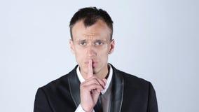 与手指的商人沈默安静的姿态 免版税库存图片