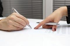 与手指的女实业家点在报名参加合同的纸 免版税库存照片