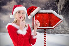 与手指的女性圣诞老人在站立在降雪的嘴唇 免版税库存照片