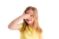 与手指的白肤金发的凹进的孩子女孩掩藏的眼睛 库存图片