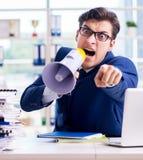 与手提式扬声机扩音器的恼怒的积极的商人在办公室 库存照片