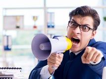 与手提式扬声机扩音器的恼怒的积极的商人在办公室 免版税库存照片