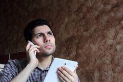 与手机和片剂认为的阿拉伯商人 免版税库存照片