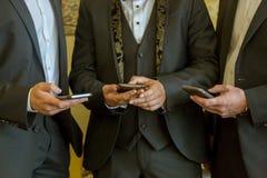 与手机的三个商人 有当代手机的人们 图库摄影