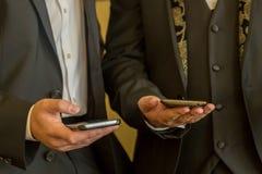 与手机的两个商人 有当代手机的人们 库存图片