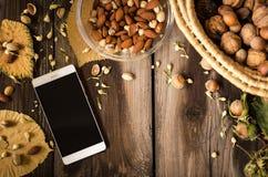 与手机的健康快餐在户内土气桌上秋天 图库摄影