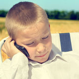 与手机的哀伤的孩子 免版税库存图片