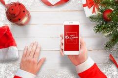 与手机的圣诞老人在工作书桌上 与装饰、礼物和灯笼的圣诞树在白色木书桌上 免版税库存图片