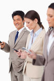 与手机的微笑的商人在同事旁边 免版税库存照片