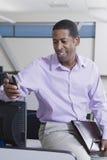 与手机的微笑的非裔美国人的商人 免版税库存图片