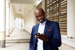 与手机的愉快的更老的非洲商人 免版税库存照片