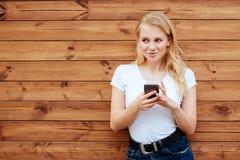 与手机的有吸引力的笑的女性身分反对木墙壁背景 免版税图库摄影