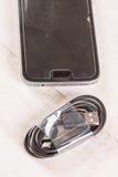 与手机的未使用的黑色usb缆绳在背景中 库存照片