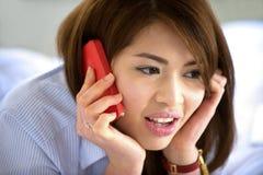 与手机的泰国青少年的女孩微笑 免版税库存图片