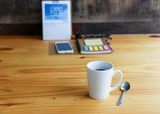 与手机的热的咖啡在木桌上 免版税库存照片