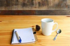 与手机的热的咖啡在木桌上 免版税库存图片