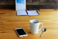 与手机的热的咖啡在木桌上 库存图片