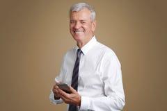 与手机的资深商人 免版税图库摄影