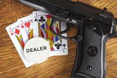 与手枪的非法赌博的概念和纸牌游戏手和经销商切削 免版税库存图片