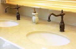 在公共厕所的水槽和轻拍 免版税库存照片