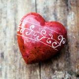 与手被刻记的样式的浪漫红色心脏 免版税库存图片