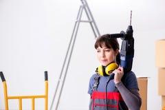与手钻的妇女承包商在建造场所 图库摄影