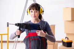 与手钻的妇女承包商在建造场所 免版税库存图片