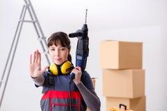 与手钻的妇女承包商在建造场所 库存图片
