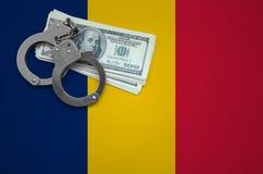 与手铐的乍得旗子和捆绑美元 打破法律和窃贼罪行的概念 免版税库存图片