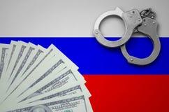 与手铐的俄罗斯旗子和捆绑美元 非法银行业务的概念在美国货币的 库存照片