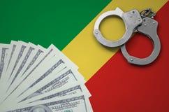与手铐的刚果旗子和捆绑美元 非法银行业务的概念在美国货币的 图库摄影