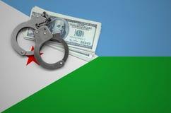 与手铐的吉布提旗子和捆绑美元 打破法律和窃贼罪行的概念 免版税库存图片