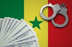 与手铐的塞内加尔旗子和捆绑美元 非法银行业务的概念在美国货币的 库存照片
