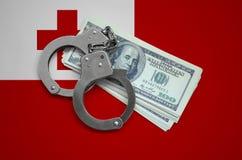 与手铐的汤加旗子和捆绑美元 货币腐败在国家 财政罪行 免版税图库摄影