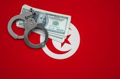 与手铐的突尼斯旗子和捆绑美元 打破法律和窃贼罪行的概念 库存图片