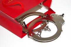 与手铐的红色购物袋 免版税库存照片