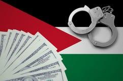 与手铐的约旦旗子和捆绑美元 非法银行业务的概念在美国货币的 库存照片